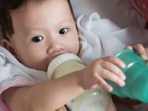 Il bambino asiatico mangia il latte dalla bottiglia Immagini Stock Libere da Diritti
