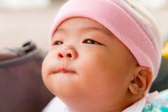 Il bambino asiatico morde il suo orlo Immagini Stock Libere da Diritti