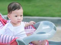 Il bambino asiatico si siede nella mattina all'aperto del passeggiatore Fotografie Stock