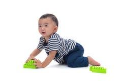 Il bambino asiatico sta giocando con i giocattoli di plastica della costruzione sopra bianco immagini stock libere da diritti