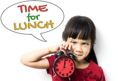 Il bambino asiatico sta tenendo l'orologio che deve andare per pranzo fotografia stock libera da diritti
