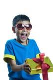 Il bambino asiatico sui sunglass si sorprende ottenere il regalo di Natale Fotografia Stock