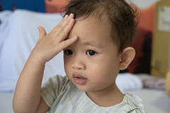 Il bambino asiatico tiene una mano per una testa Fotografia Stock