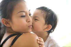 Il bambino bacia la sua mamma sulla sua guancica fotografia stock