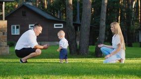 Il bambino bacia il padre Giovane famiglia felice che gioca con il loro figlio di 1 anno nell'iarda stock footage