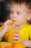 Il bambino beve la spremuta Fotografia Stock
