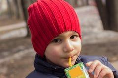 Il bambino beve il succo nel campo da giuoco Ritratto emozionale del primo piano fotografie stock