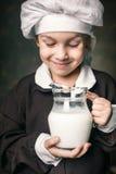 Il bambino beve un bicchiere di latte fotografia stock libera da diritti