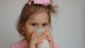 Il bambino beve una bevanda a base di latte - il kefir, i frullati, il cocktail, yogurt Una bambina piacevole che tiene un vetro  video d archivio
