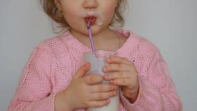 Il bambino beve una bevanda a base di latte - il kefir, i frullati, il cocktail, yogurt Una bambina piacevole che tiene un vetro  archivi video