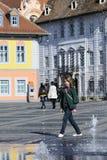 Il bambino bianco che ha divertimento vicino alla fontana quadrata cade Fotografie Stock Libere da Diritti