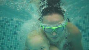Il bambino biondo sveglio sta tuffandosi sotto l'acqua insieme a sua madre in vetri di protezione speciali nel nuoto archivi video
