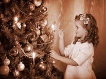 Il bambino brucia le candele sull'albero di Natale. Immagini Stock Libere da Diritti
