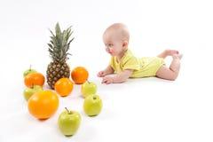 Il bambino in buona salute sorridente sveglio si trova su un fondo bianco fra il frui fotografia stock