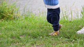 Il bambino cammina all'aperto, i primi punti del bambino, mamma va dopo Vista laterale, primo piano archivi video