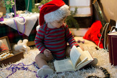Il bambino in cappello di Santa ha letto un libro Fotografie Stock