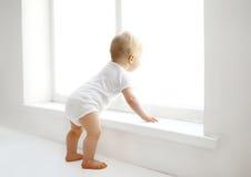 Il bambino a casa nella stanza bianca sta la finestra vicina fotografie stock