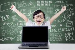 Il bambino celebra il suo successo con il computer portatile nella classe Fotografia Stock Libera da Diritti