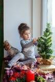 Il bambino che decora l'albero di Natale sul davanzale con fa Fotografia Stock