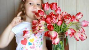 Il bambino che fiuta un fiore del tulipano e starnutisce e graffia il suo naso Allergia ai fiori stock footage
