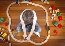 Il bambino che gioca con i giocattoli si prepara e railroad mentre si siede sul pavimento di legno nella sua stanza Vista superio fotografia stock
