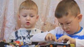 Il bambino che gioca il gioco intellettuale, raccoglie il progettista, sulla tavola closeup stock footage
