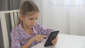 Il bambino che gioca la compressa, bambino usa la vista interna di Smartphone, cuscinetto mandante un sms della bambina immagini stock