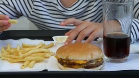 Il bambino che mangia gli alimenti a rapida preparazione, bambino mangia l'hamburger in ristorante, succo bevente della ragazza video d archivio