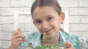 Il bambino che mangia l'insalata verde, bambino in cucina, ragazza mangia l'alimento verdura e sano fresco fotografie stock
