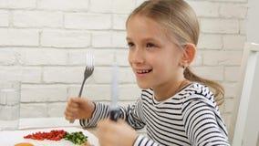 Il bambino che mangia la prima colazione in cucina, bambino mangia le uova sane dell'alimento, verdure della ragazza stock footage