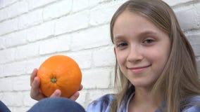 Il bambino che mangia le arance fruttifica alla prima colazione, bambino della ragazza che odora la cucina sana dell'alimento video d archivio