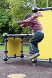 Il bambino che salta al campo da giuoco Fotografia Stock