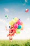 Il bambino che salta con il giocattolo balloons nel giacimento di primavera Fotografie Stock Libere da Diritti