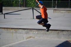 Il bambino che salta mentre pattina Fotografia Stock