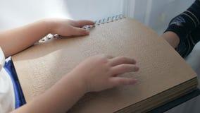 Il bambino cieco sta leggendo Braille con aiuto delle mani stock footage