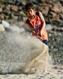 Il bambino colpisce una sfera di golf alla spiaggia Immagine Stock