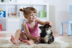 Il bambino con il cane che si siede sul pavimento a casa Fotografia Stock