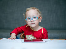 Il bambino con i vetri si siede ad una tavola sui precedenti della tavola per un esame degli occhi Fotografie Stock Libere da Diritti