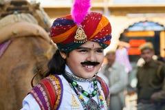 Il bambino con il fronte felice mostra il bello costume indiano Immagine Stock