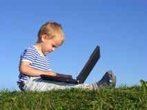 Il bambino con il taccuino si siede il cielo blu 2