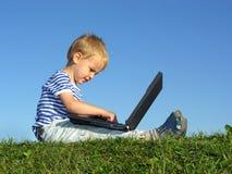 Il bambino con il taccuino si siede il cielo blu Fotografia Stock
