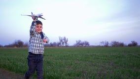 Il bambino con l'aeroplano del giocattolo in mani funziona all'aperto su fondo del campo e del cielo archivi video
