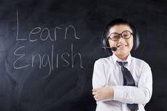 Il bambino con la cuffia avricolare ed il testo imparano l'inglese Fotografie Stock