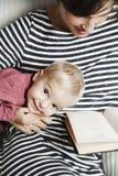 Il bambino con la madre sta leggendo un libro Immagini Stock Libere da Diritti