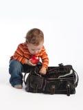 Il bambino con la mela apre la chiusura lampo del sacchetto femminile Fotografie Stock Libere da Diritti