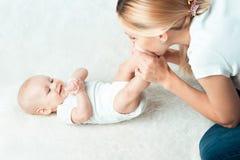 Il bambino con la mummia sta facendo il massaggio Fotografie Stock Libere da Diritti