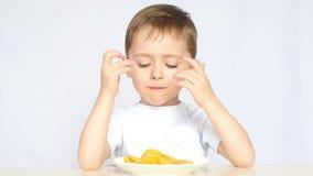 Il bambino con piacere e gioia, mangiando le patatine fritte, sedentesi alla tavola su un fondo bianco Il ragazzo ama croccante video d archivio