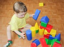 Il bambino costruisce un castello dal progettista di plastica Un ragazzino Immagine Stock