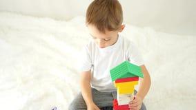Il bambino costruisce una casa dei blocchi colorati su un fondo bianco Il ragazzo felice sta giocando Il concetto di sviluppo inf video d archivio