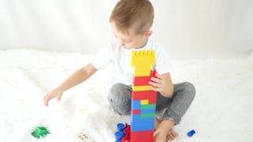 Il bambino costruisce una torre dei blocchi colorati su un fondo bianco Il concetto di sviluppo infantile Vista da sopra stock footage